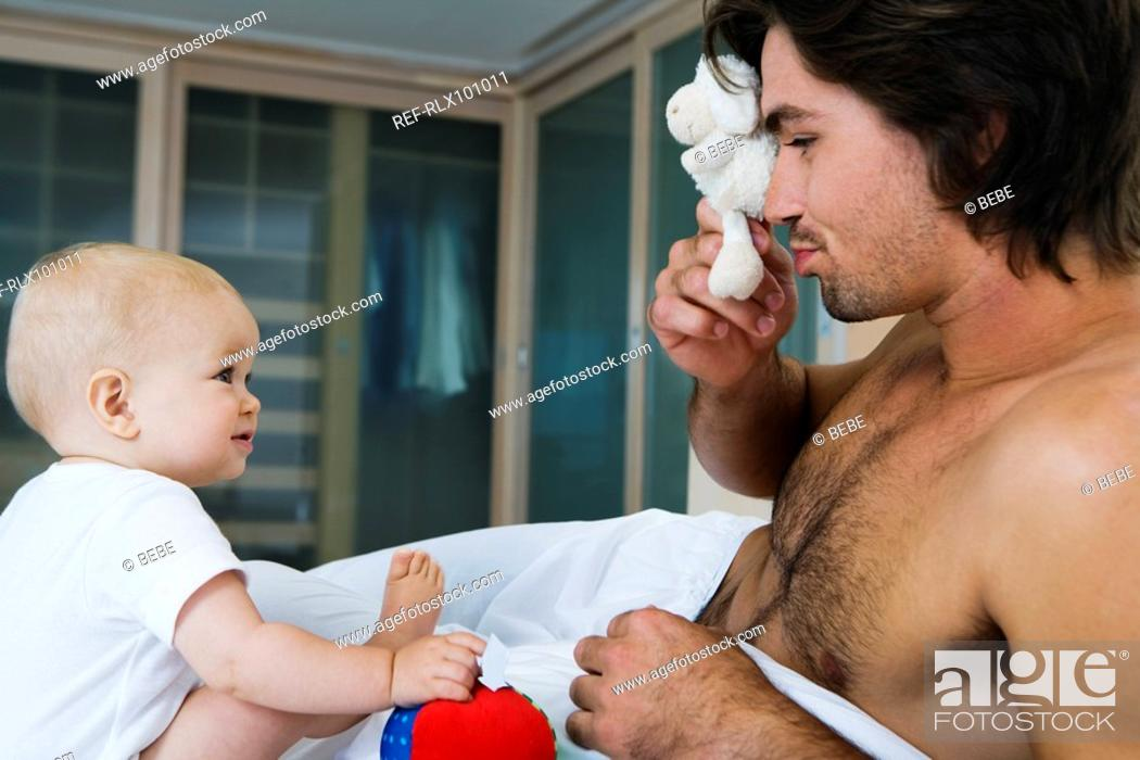 Stock Photo: Young father playing with baby 6-12 months in bed, looking at baby, with toys.