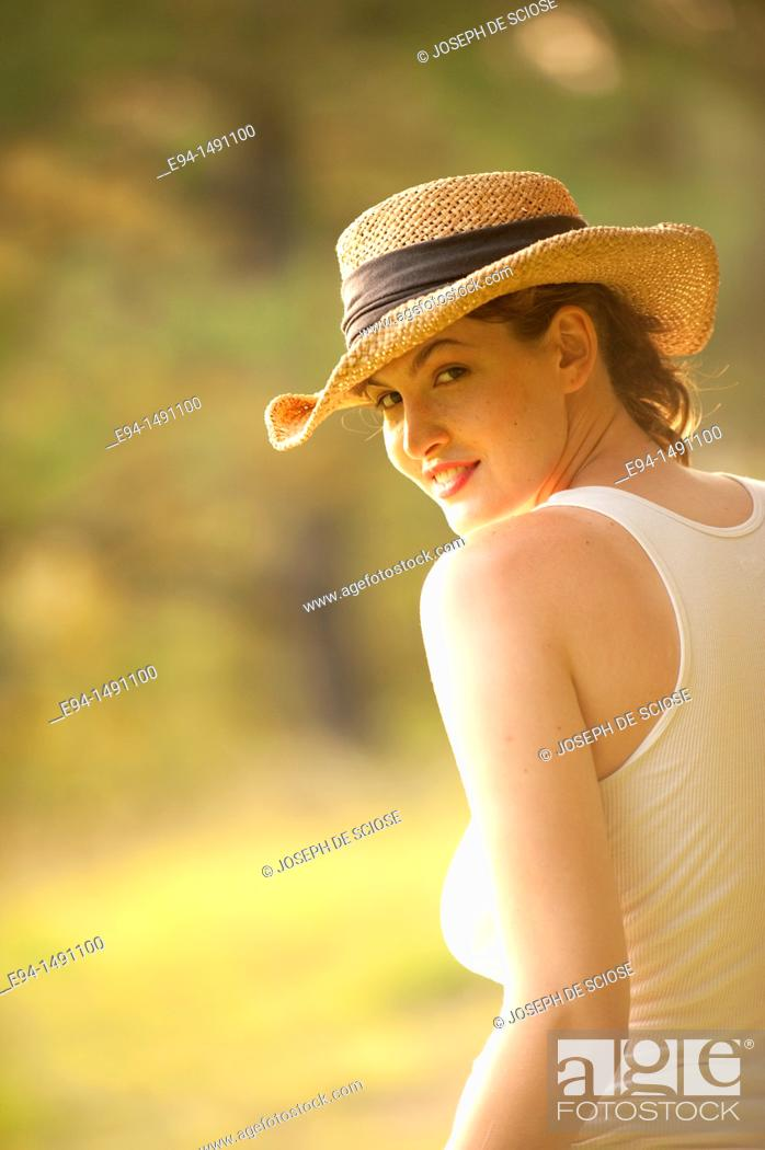 Stock Photo: Casuual portrait of a 21 year old brunette woman in a country outdoor setting wearing a tank top and a straw hat.