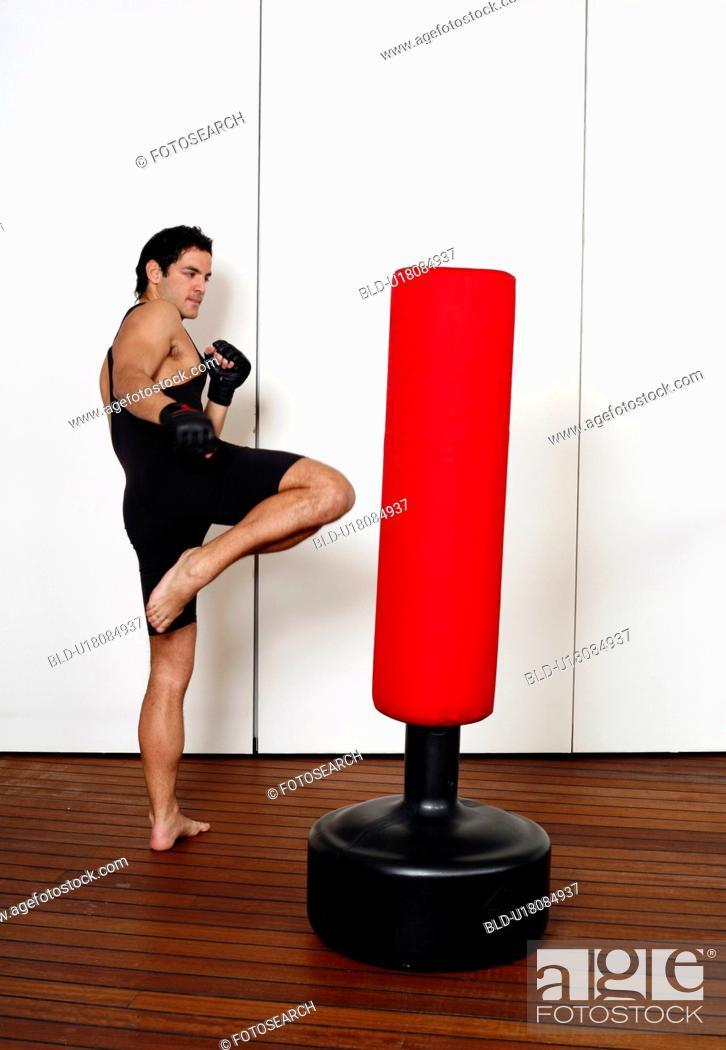 Stock Photo: Young man kicking a punching bag.