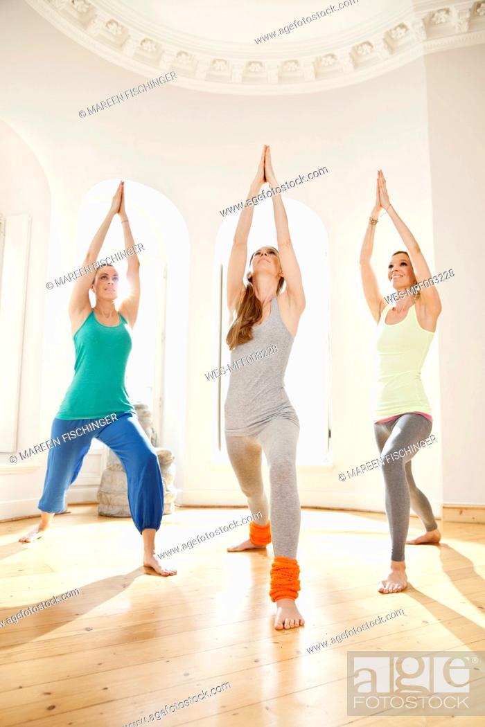 Stock Photo: Three women in sunny yoga studio holding Virabhadrasana pose.