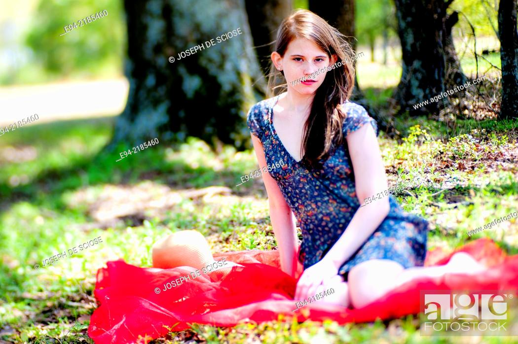 Stock Photo: A 22 year old brunette woman wearing a summer dress sitting on a blanket in a pasture.