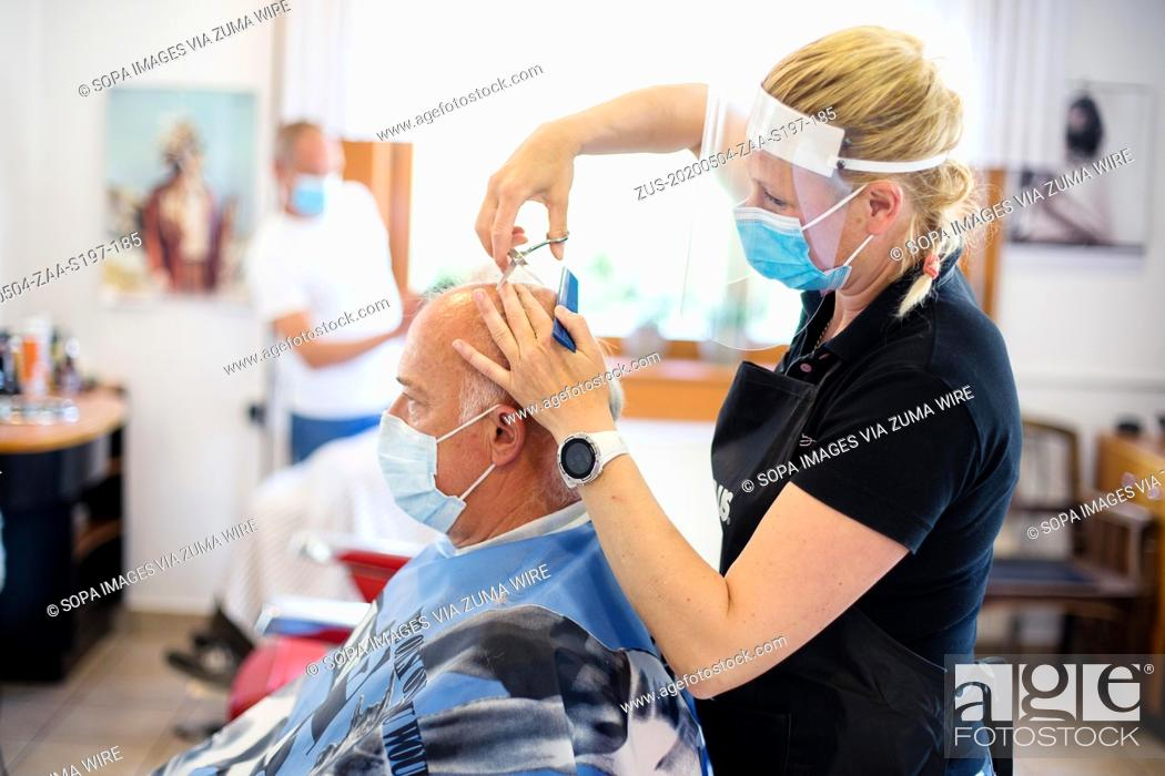 Photo de stock: May 4, 2020, Kranj, Slovenia: A hairdresser wearing a face mask and shield as preventive measure cuts hair of a client amid coronavirus crisis.