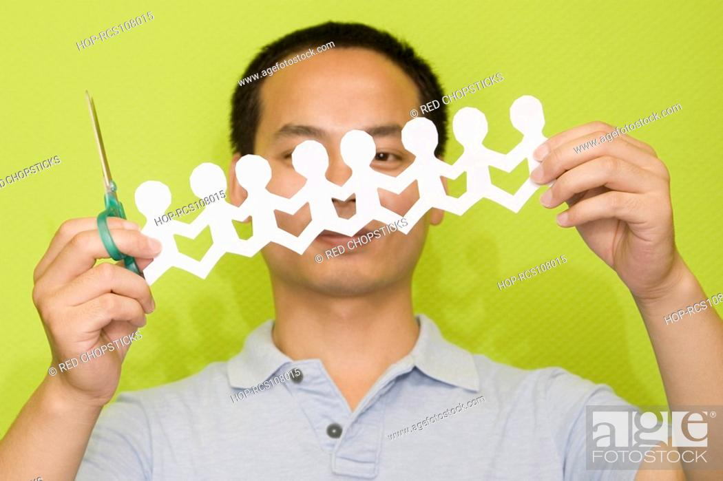 Stock Photo: Close-up of a male office worker holding a pair of scissors and a paper chain.