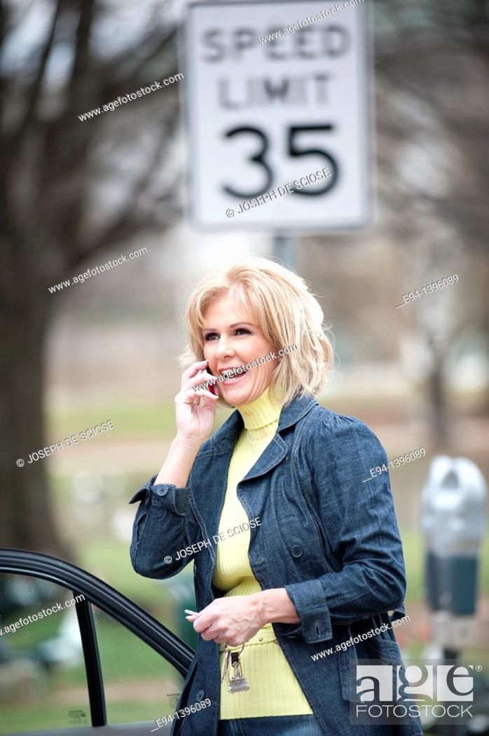 Stock Photo: Fifty year old blond woman talking on a mobile phone, outdoors near a car.