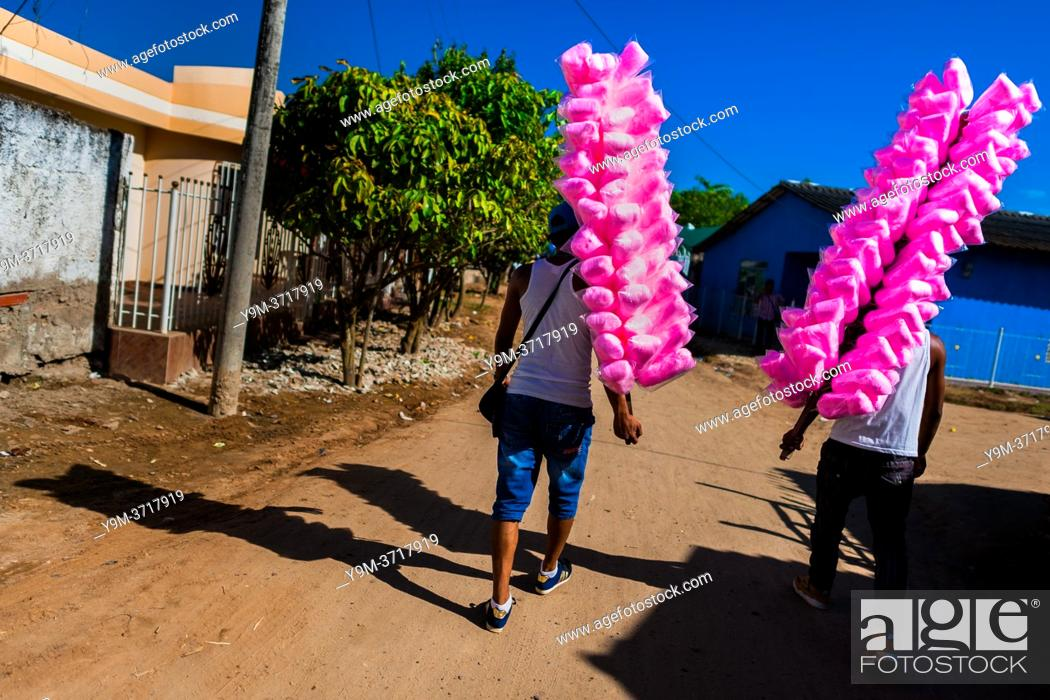 Stock Photo: Colombian street vendors, carrying cotton candy bags for sale, walk towards the arena of Corralejas, a rural bullfighting festival held in Soplaviento, Colombia.