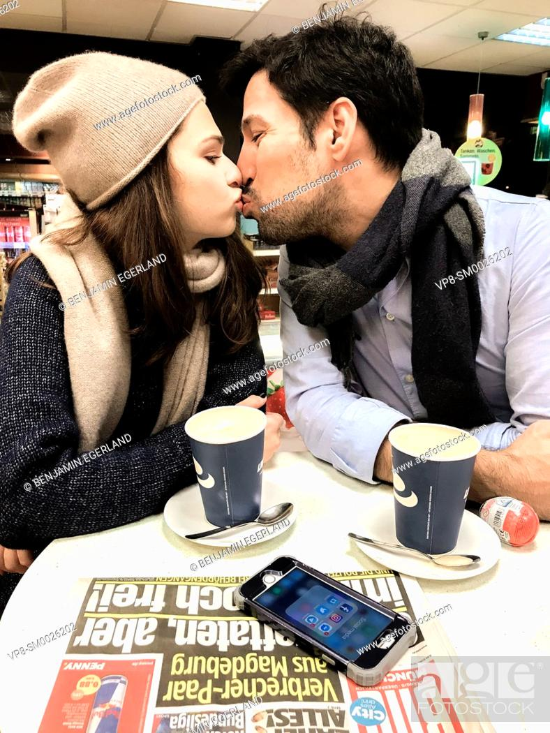 Imagen: couple kissing while taking a break at table at gas station's café with newspaper Bild and phone laying on table and paper cups of coffee in Munich, Germany.