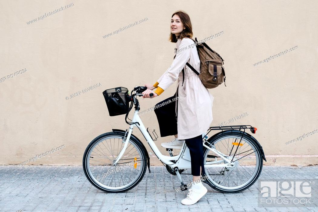 Stock Photo: Woman with e-bike at a wall.