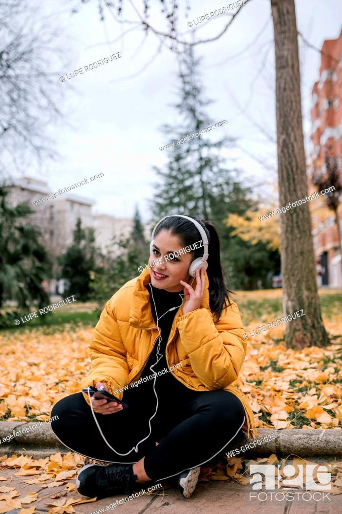 Stock Photo: Portrait of smiling young woman listening music with headphones and smartphone in autumn.