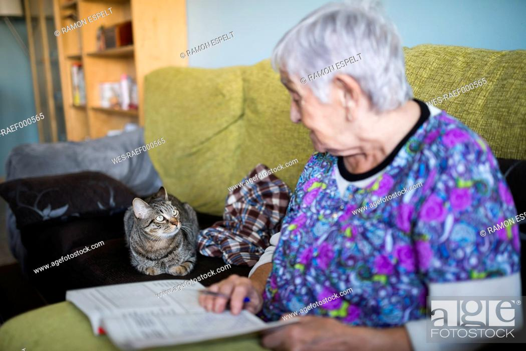 Stock Photo: Senior woman and tabby cat on the couch at home looking at each other.