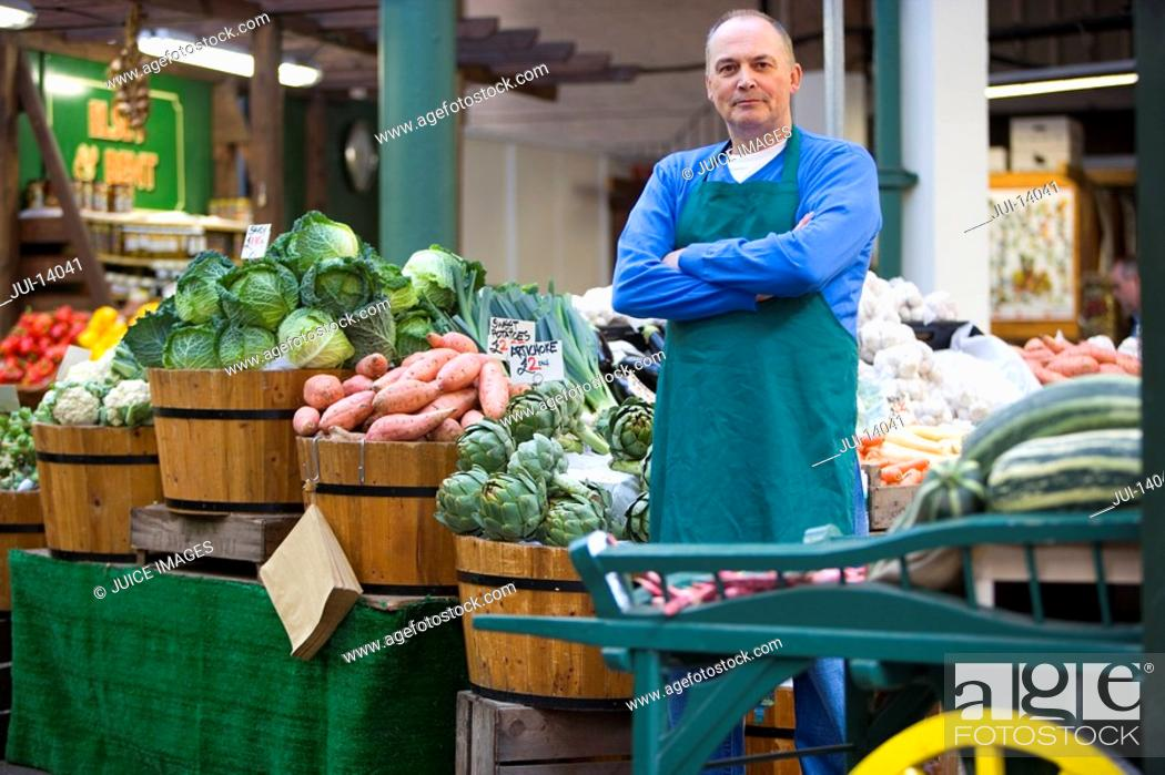 Stock Photo: Green grocer with arms crossed by produce, portrait.