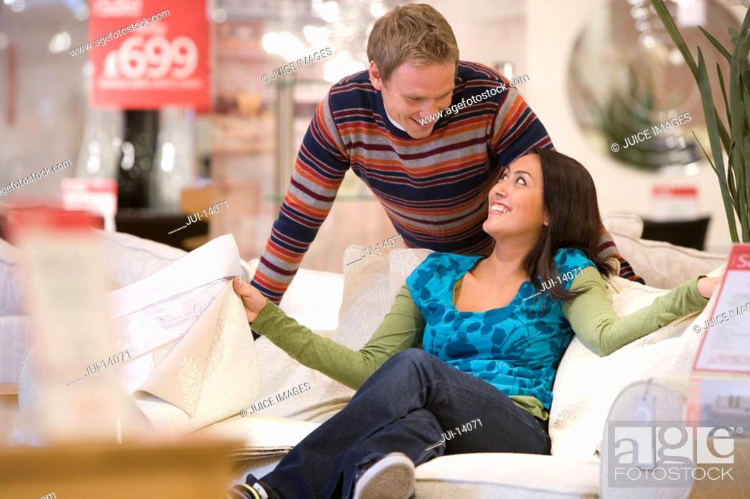 Stock Photo: Young couple shopping, man smiling at woman on sofa.