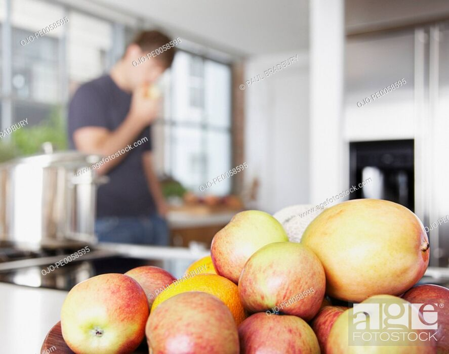 Stock Photo: Bowl of mangos and nectarines with man in background eating.