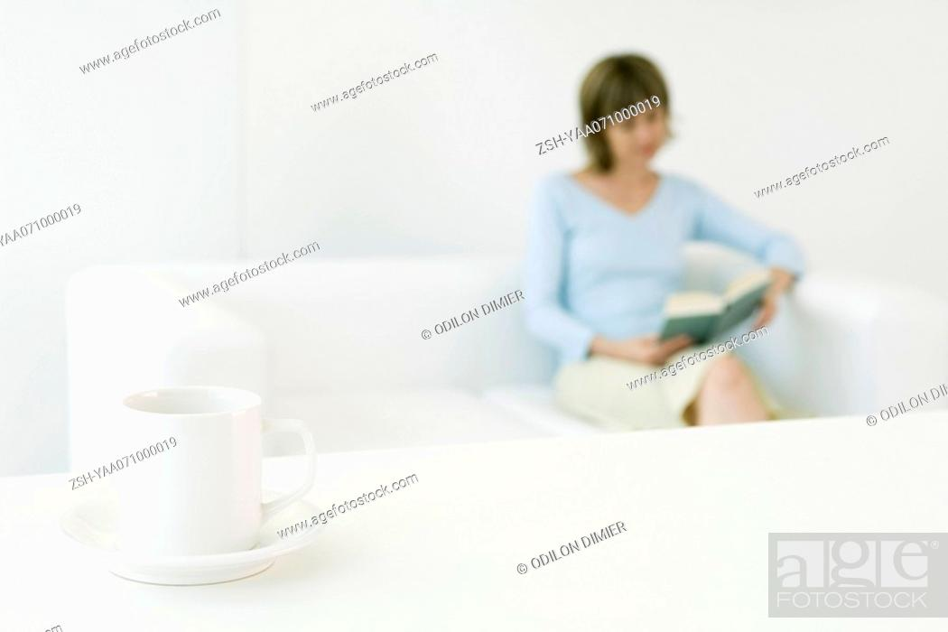 Stock Photo: Woman reading book on sofa, focus on coffee cup in foreground.