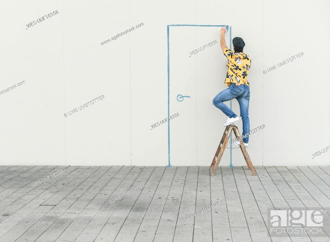 Stock Photo: Digital composite of young man drawing a door at a wall.