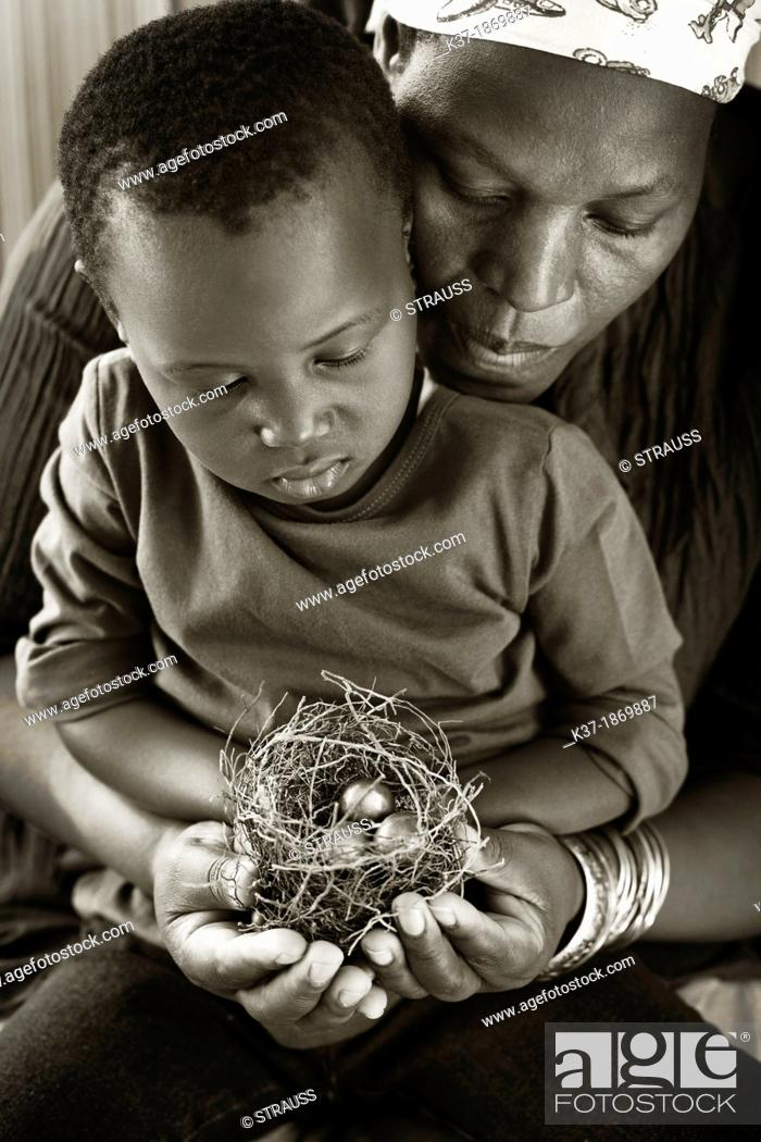 Stock Photo: Black mother with child looking at nest with egg.