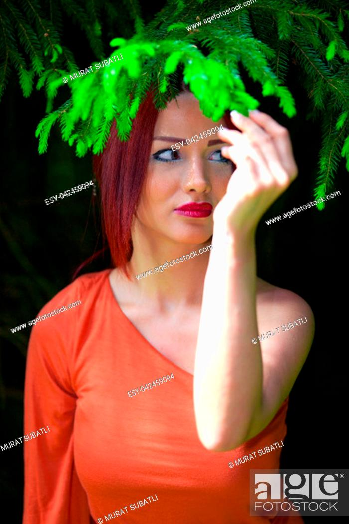 Stock Photo: Redhead with orange dress in the forest.