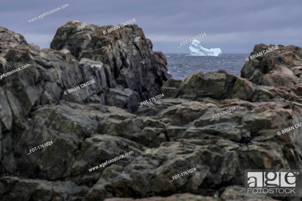 Stock Photo: View of iceberg in sea through rocks on shore, Fogo Island, Newfoundland, Canada.