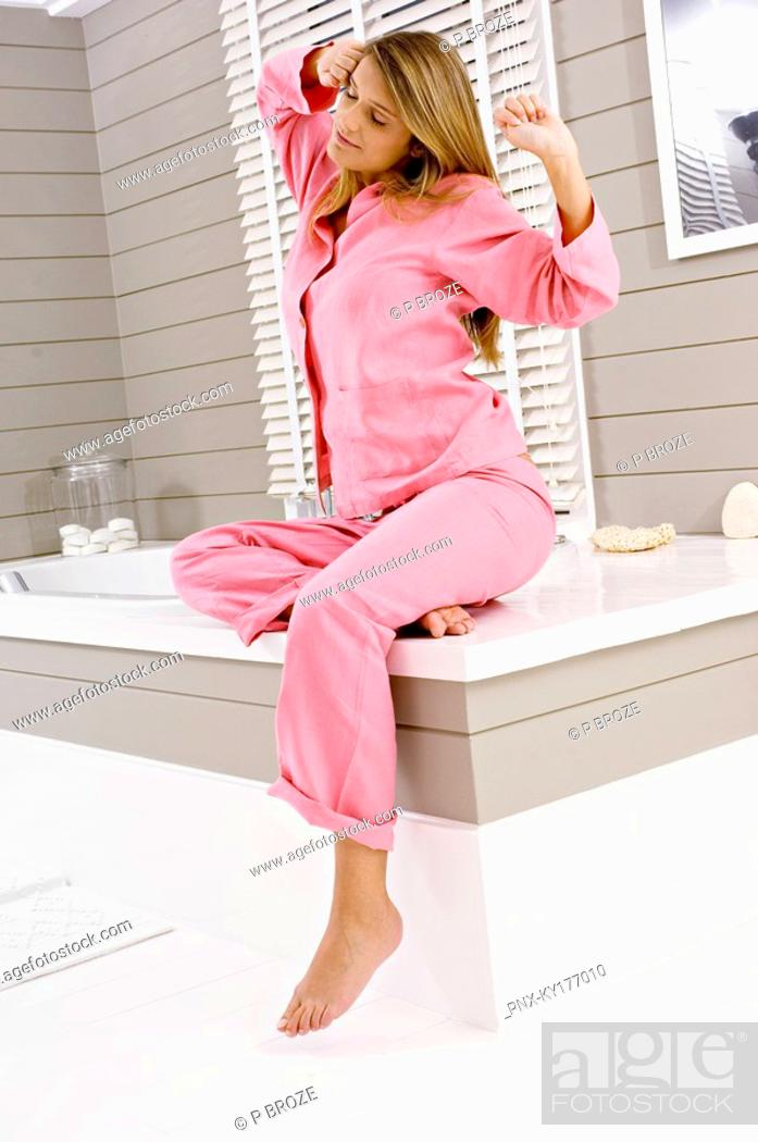 Stock Photo: Young woman sitting on a bathtub and stretching.