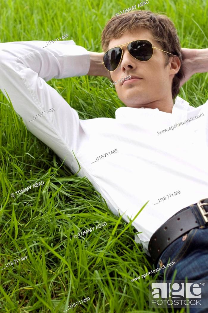 Stock Photo: a man laying down on the grass.