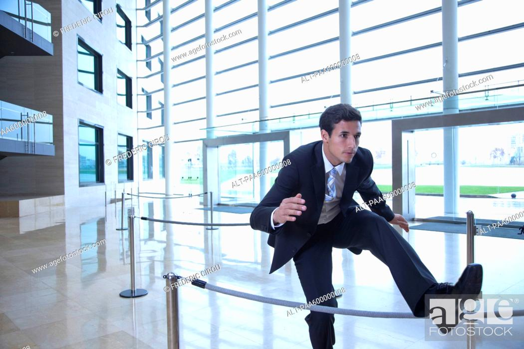 Stock Photo: Businessman jumping over rope in lobby.