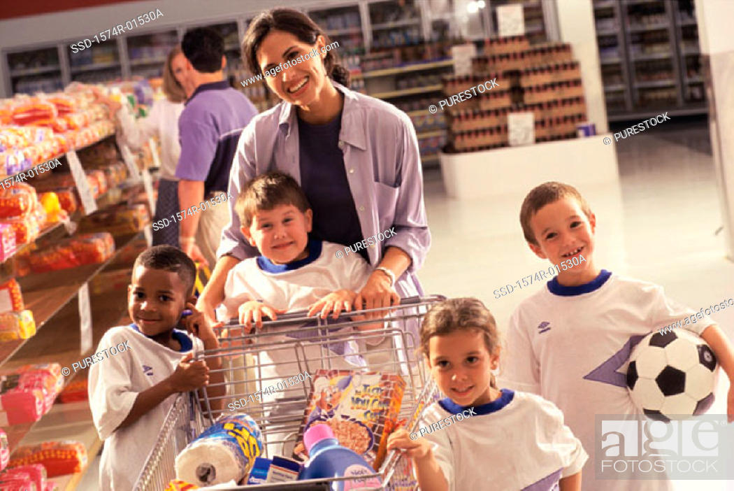 Stock Photo: Portrait of a woman grocery shopping with four children from a football team.
