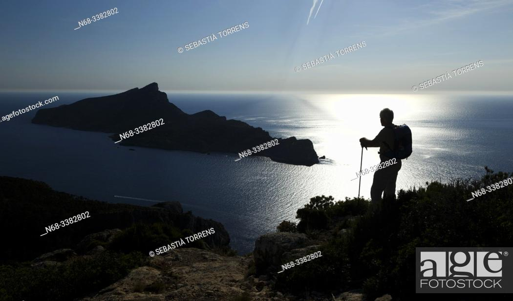 Imagen: Backlight view of the island of Sa Dragonera from Andratx coast with hiker, Mallorca, Spain.