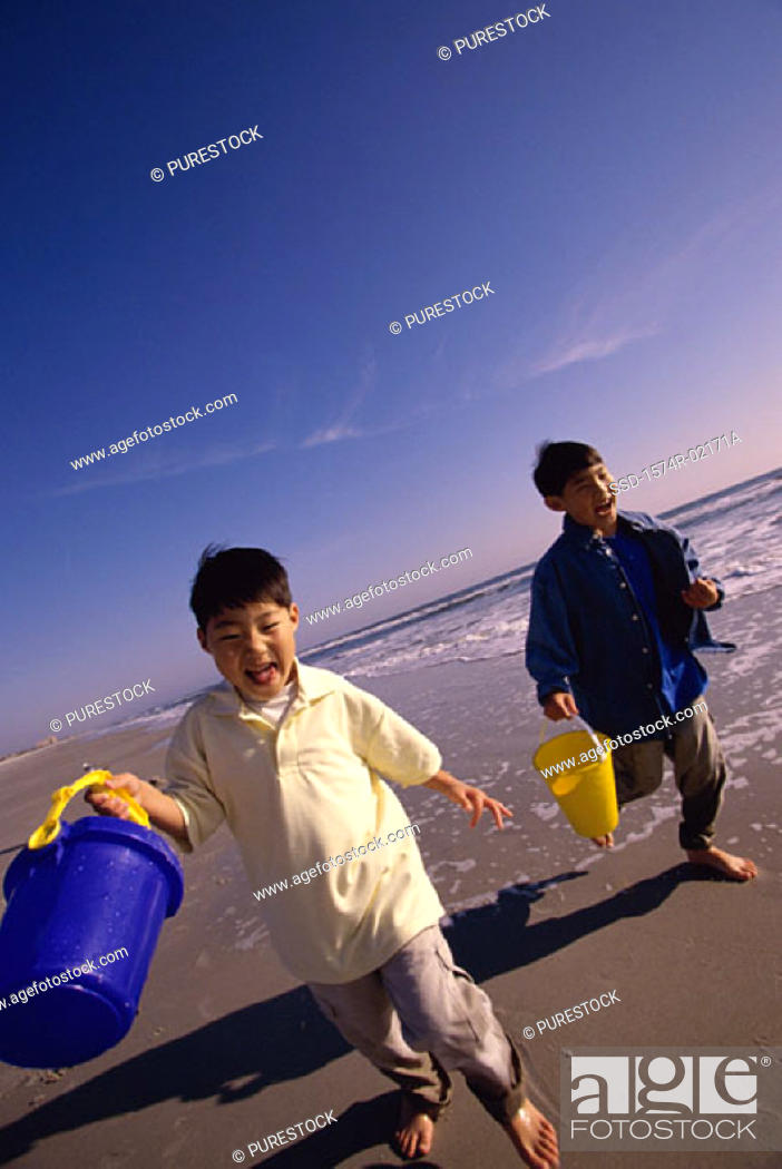Stock Photo: Two boys running with sand pails on the beach.