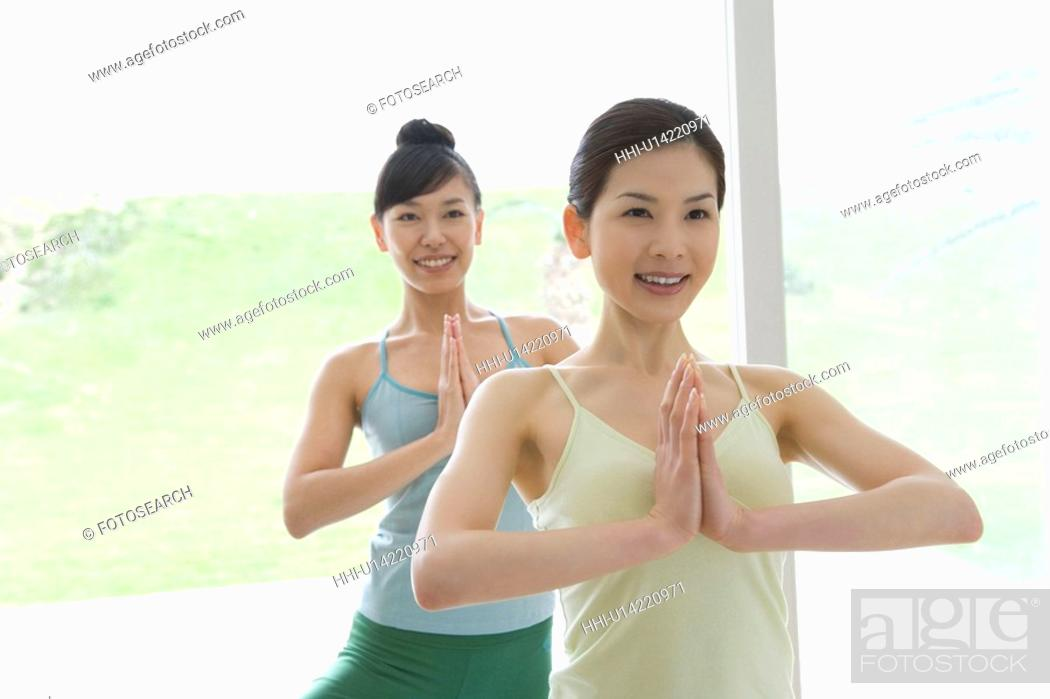 Stock Photo: Young women doing yoga exercise, front view.