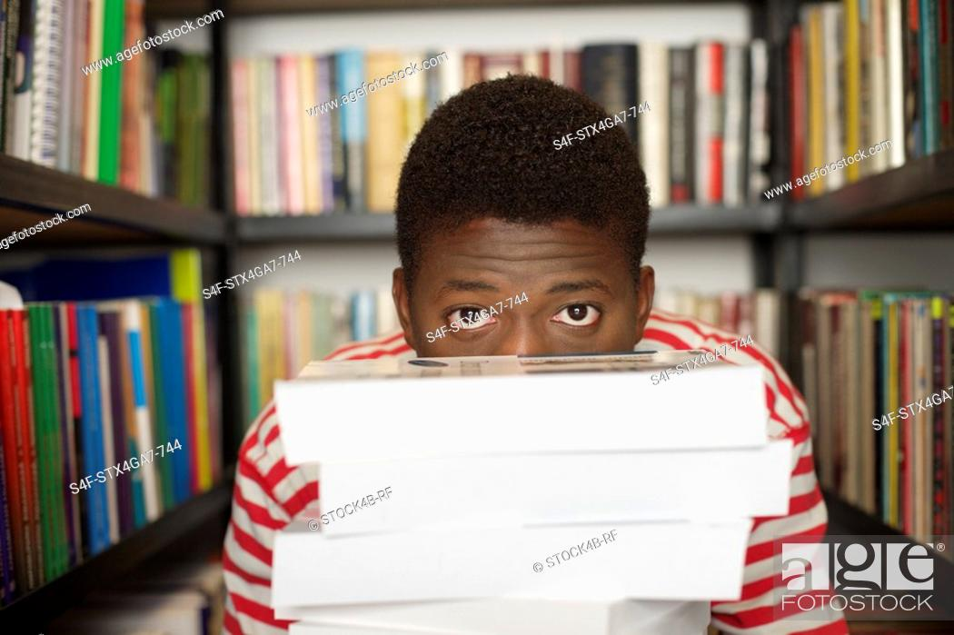 Stock Photo: Student behind a stack of books.