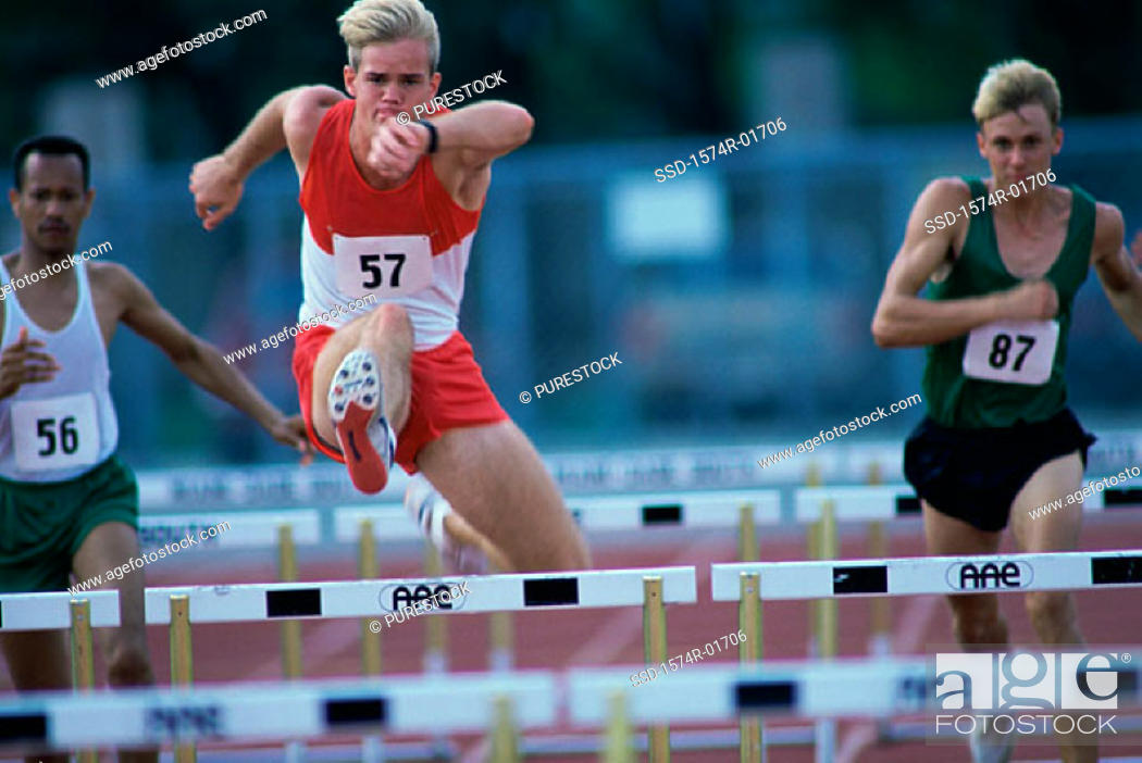 Stock Photo: Male runners jumping hurdles in a race.