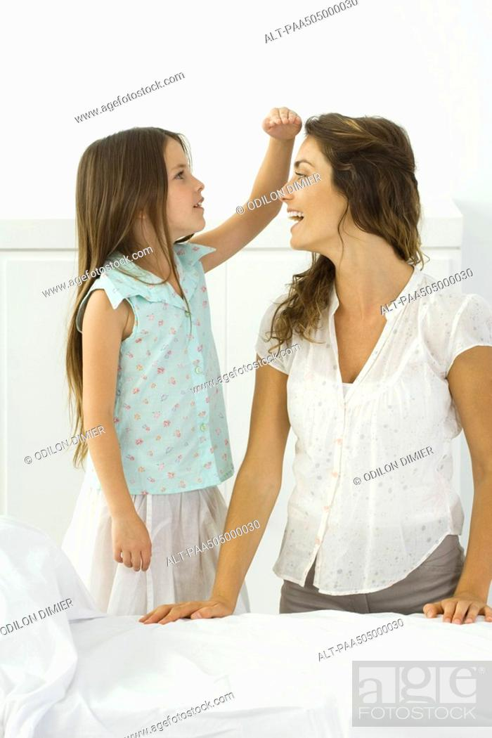 Stock Photo: Little girl standing beside kneeling mother, comparing height with her hand.
