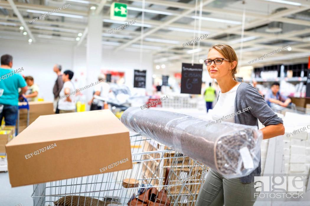 Stock Photo: Pretty, young woman choosing the right furniture for her apartment in a modern home furnishings store - with a trolley, done shopping, leaving the store.