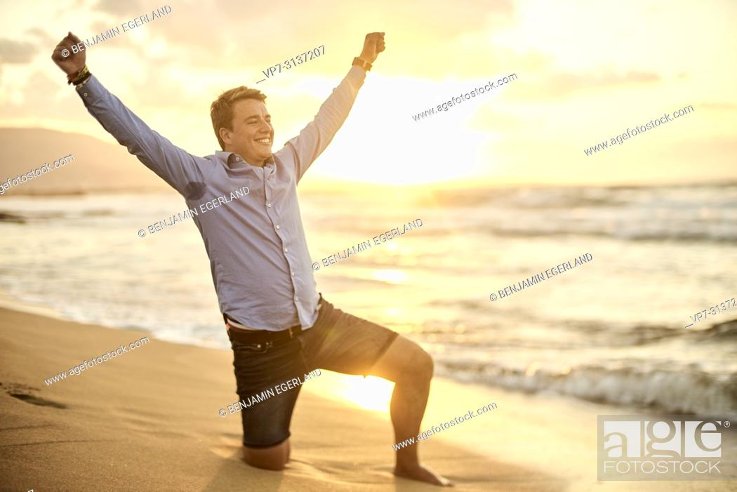 Stock Photo: Young man kneeling on Potamos beach, wearing business shirt, in holiday destination Malia, Crete, Greece.