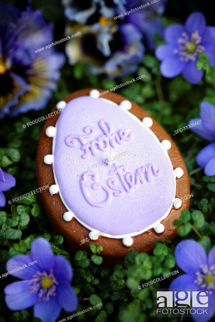 Imagen: An egg-shaped candle with the words 'Frohe Ostern' surrounded by liverwort floweers.