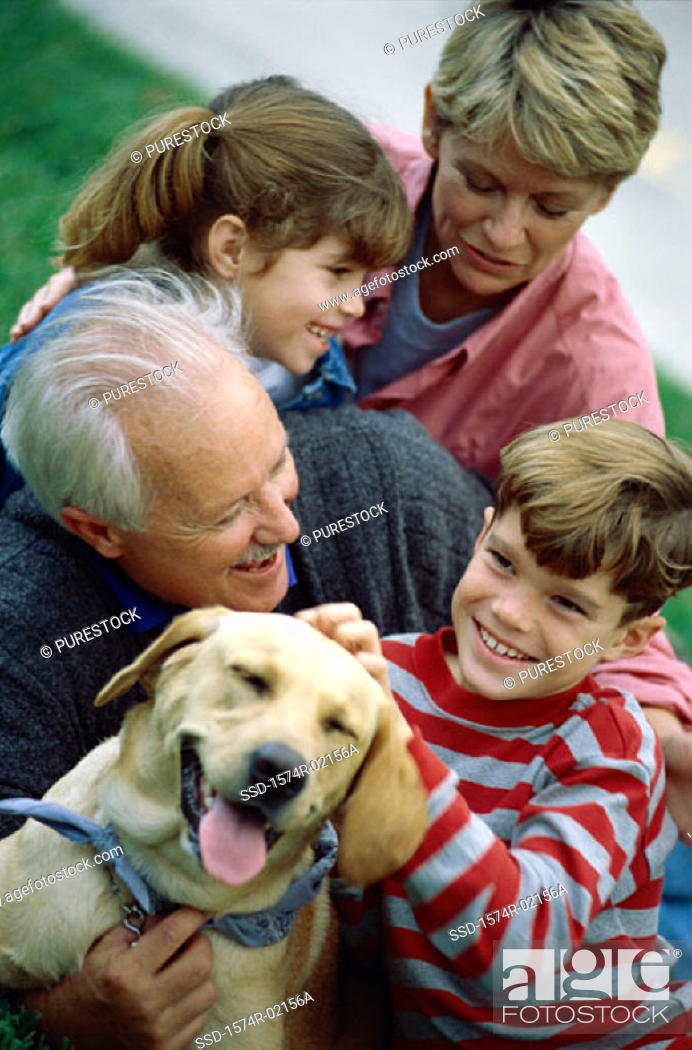 Stock Photo: Grandparents with their grandson and granddaughter holding their dog.