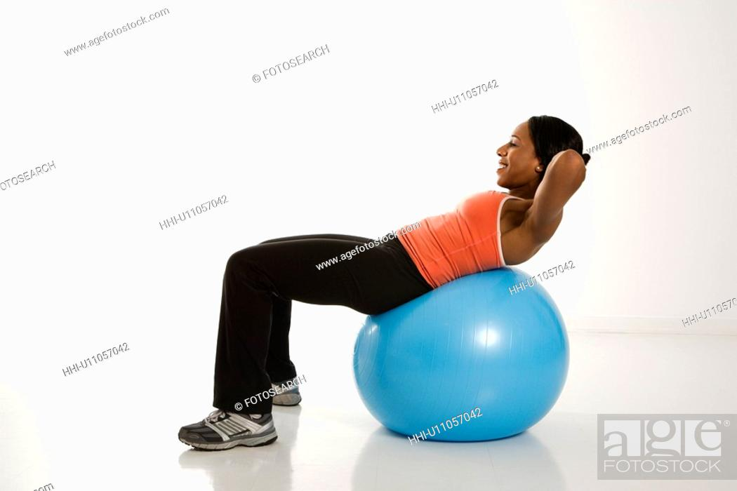 Stock Photo: Side view of African American woman balancing on exercise ball doing crunches.