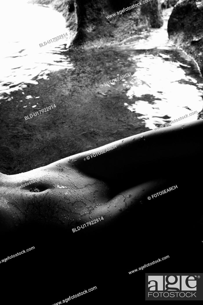 Stock Photo: Nude female hips and abdomen lying down in a cave with water.