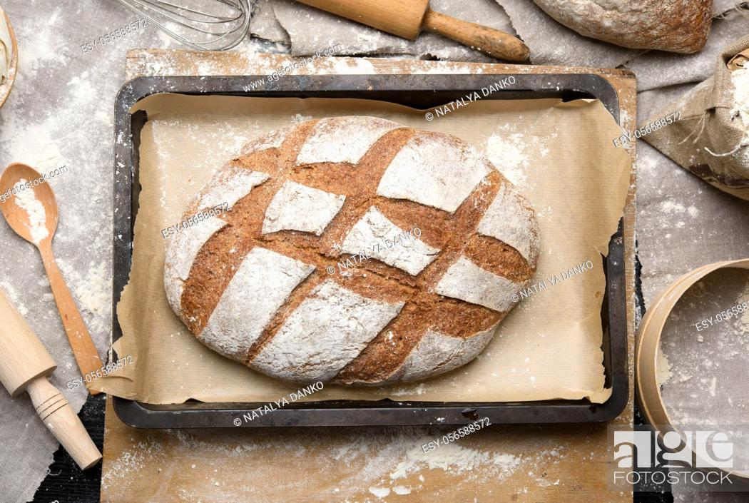 Stock Photo: baked oval rye flour bread in a metal baking sheet on the table, top view.