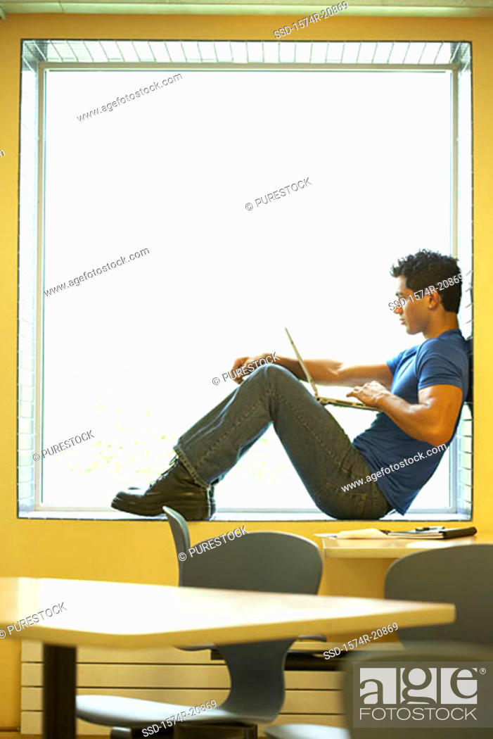 Stock Photo: Side profile of a college student sitting on a window ledge and using a laptop.