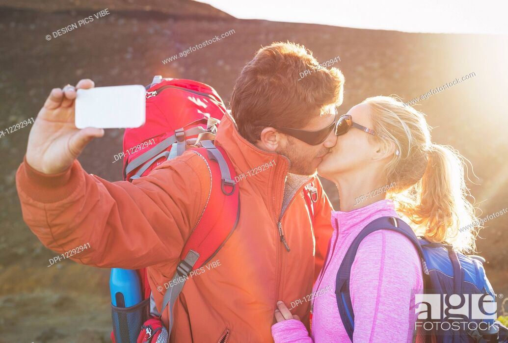 Stock Photo: Happy couple taking photo of themselves with smart phone outdoors, Taking a selfie.