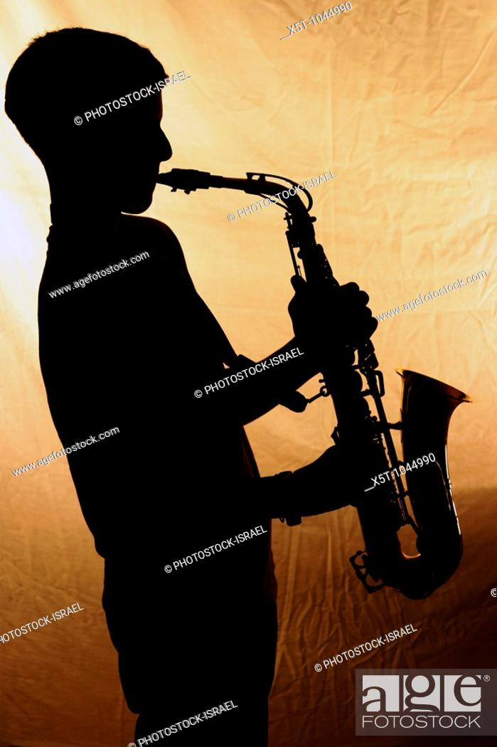 Stock Photo: Silhouette of a Saxophone player - close up.
