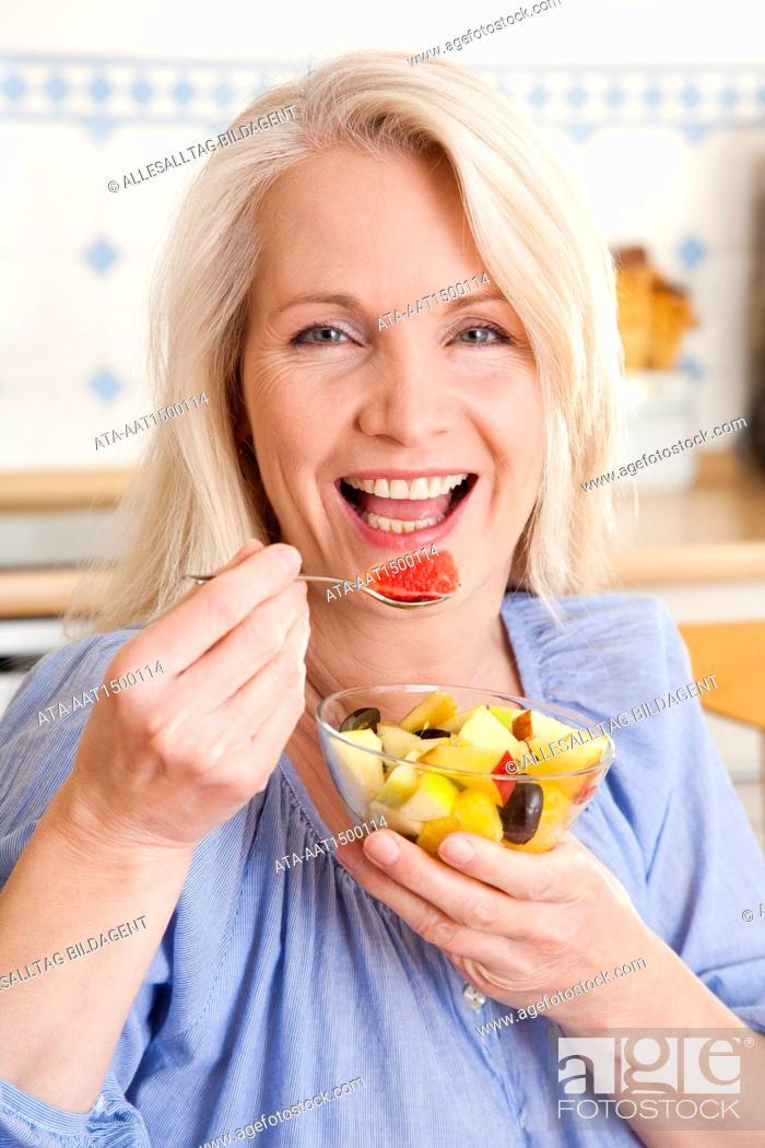 Stock Photo: Woman eating fruit salad.