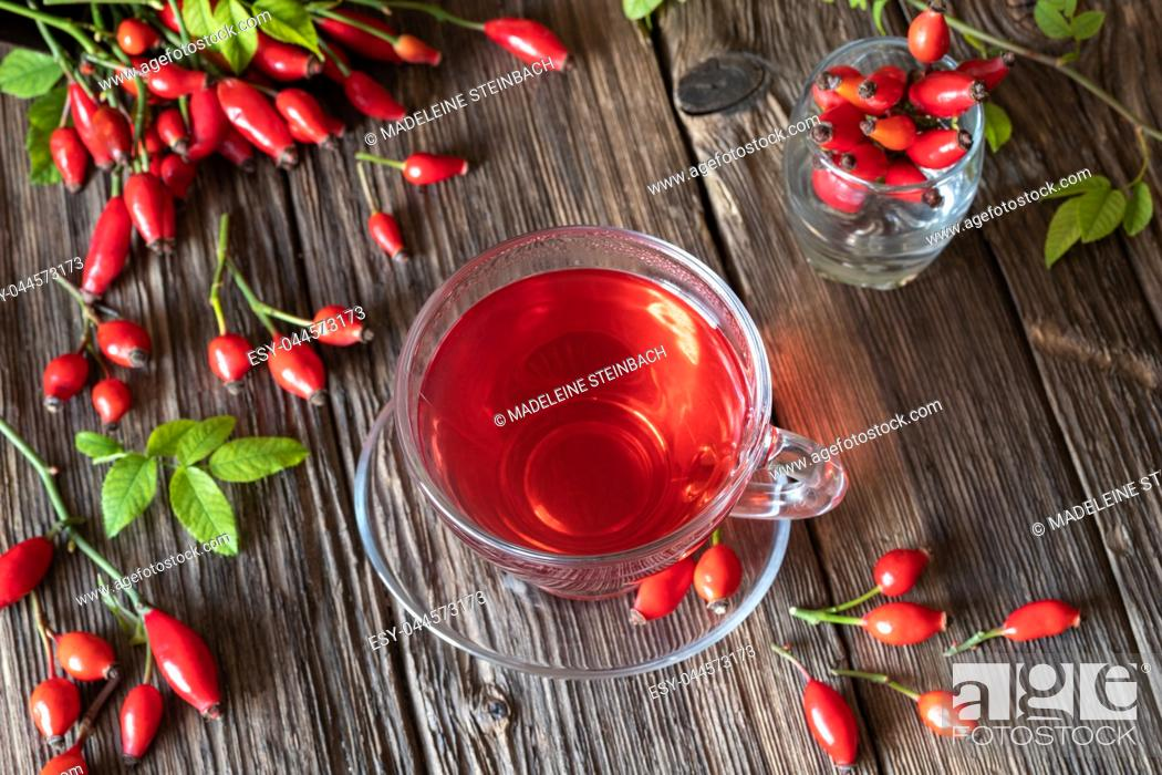 Stock Photo: A cup of rose hip tea on a wooden table, top view.