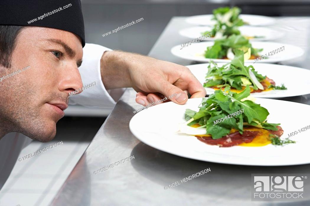 Stock Photo: Male chef preparing salad in kitchen close-up.