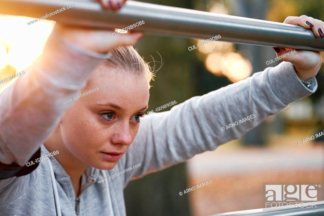 Stock Photo: Young woman training, leaning against handrail in park.