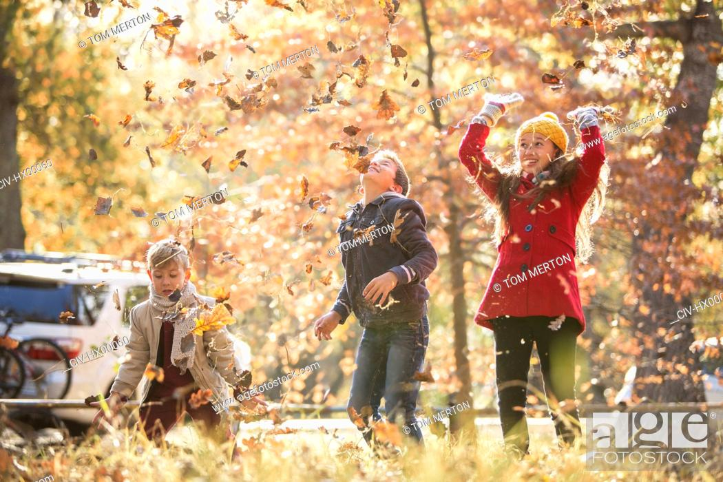 Stock Photo: Boys and girl throwing autumn leaves overhead.