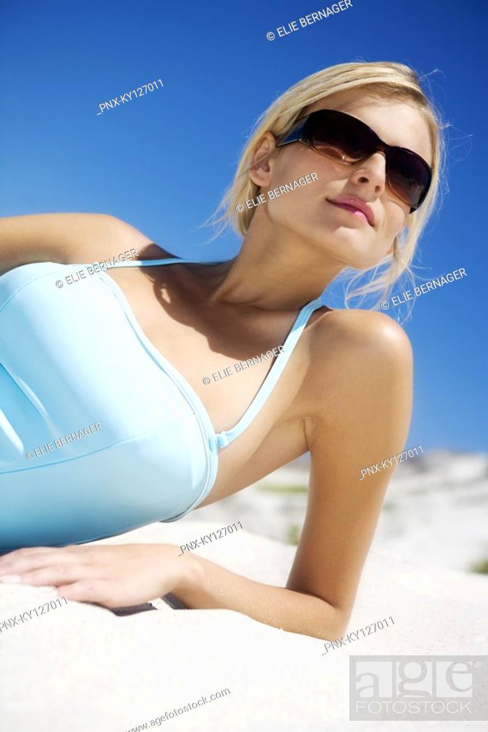 Stock Photo: Young woman in swimming costume lying on the beach, sunglasses.
