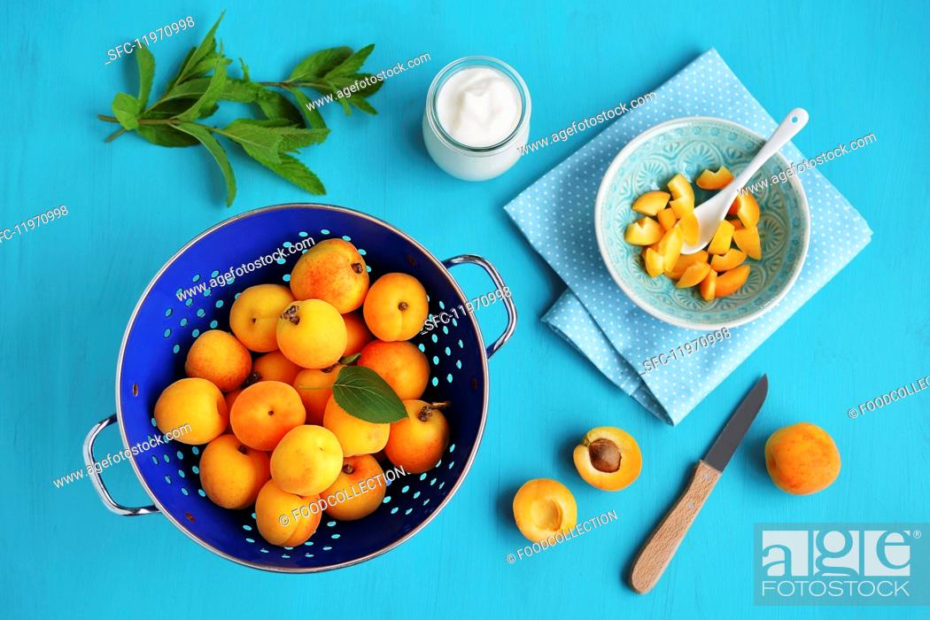Imagen: Fresh apricots in a colander and sliced in a bowl.