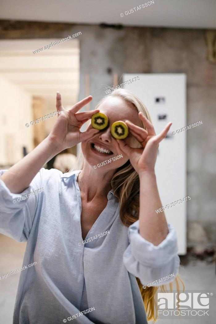 Stock Photo: Happy young woman covering her eyes with kiwis.