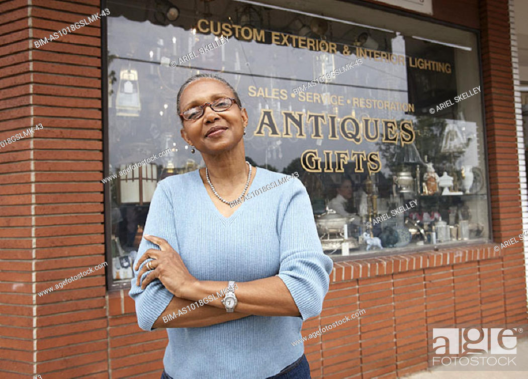 Stock Photo: Mature woman standing in front of antique shop.